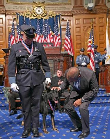 Ashland Police Officer Christopher E. Alberini along with his partner Dax were awarded the Medal Of Valor. Governor Patrick gave Dax a pat on the head.  Photo by:  David L Ryan/Globe Staff