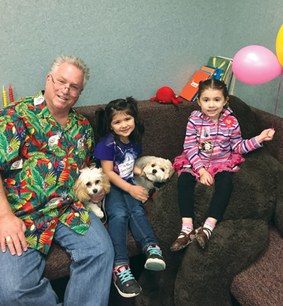 Lexa and Flossie: (From left) Dr. Alan Golden, Elysia Yriarte and Natalia Caraballo smile for the camera while petting Flossie, a dental therapy dog, and her half-sister Lexa, a dental therapy dog-in-training.  (photo courtesy of American Dental Association)